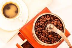 Molino de café y taza de café retros en el fondo blanco Imágenes de archivo libres de regalías