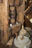 Molino de piedra antiguo: Amoladora manual Wheel con la manivela y prensa de madera para las pastas imágenes de archivo libres de regalías