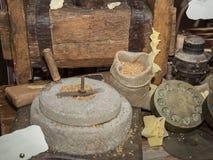 Molino de piedra antiguo: Amoladora manual Wheel con la manivela y prensa de madera para las pastas fotografía de archivo libre de regalías