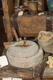 Molino de piedra antiguo: Amoladora manual Wheel con la manivela y prensa de madera para las pastas imagen de archivo