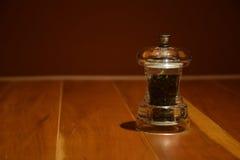 Molino de pimienta en la tabla de madera Fotos de archivo