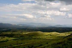 Molino de viento blanco, cielo azul, nubes blancas, montañas verdes y aguas imagenes de archivo