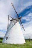 Molino de viento blanco grande debajo del cielo azul Fotos de archivo