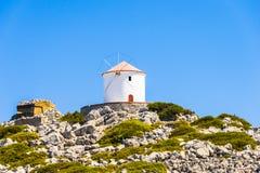 Molino de viento blanco viejo en un acantilado rocoso Fotos de archivo