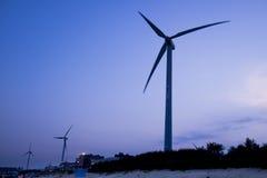 Molino de viento cerca de la playa en puesta del sol Imagen de archivo libre de regalías