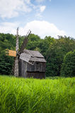 Molino de viento de madera viejo cerca de un bosque Foto de archivo libre de regalías