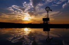 Molino de viento del rancho en la puesta del sol Fotos de archivo libres de regalías