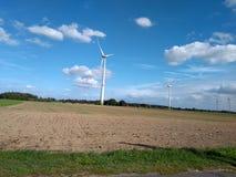 Molino de viento eléctrico de la turbina con paisaje y el cloudscape del cuento de hadas imagen de archivo libre de regalías