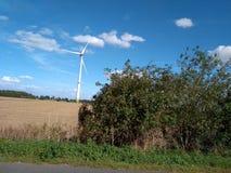 Molino de viento eléctrico de la turbina con paisaje y el cloudscape del cuento de hadas foto de archivo