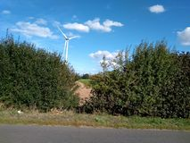 Molino de viento eléctrico de la turbina con paisaje y el cloudscape del cuento de hadas imagen de archivo