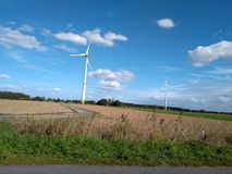 Molino de viento eléctrico de la turbina con paisaje y el cloudscape del cuento de hadas fotos de archivo