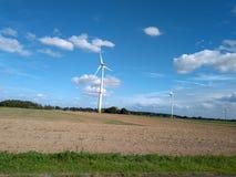 Molino de viento eléctrico de la turbina con paisaje y el cloudscape del cuento de hadas imagenes de archivo