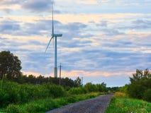Molino de viento en el camino rural en la puesta del sol Granja de las turbinas de viento Foto de archivo libre de regalías