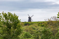 Molino de viento en la colina con tres caminantes en la cresta imagen de archivo