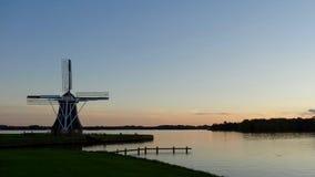 Molino de viento en la puesta del sol Imagen de archivo libre de regalías