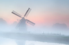 Molino de viento en niebla densa en la salida del sol del verano Foto de archivo