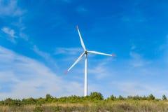 Molino de viento giratorio que genera energía eólica de la energía renovable en la tierra Imagen de archivo