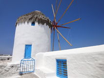 Molino de viento hermoso con la puerta azul en Mykonos Imagen de archivo