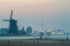Molino de viento histórico holandés con los edificios de la industria imagen de archivo libre de regalías