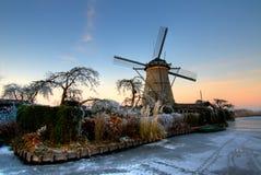 Molino de viento holandés con el jardín en la puesta del sol Imágenes de archivo libres de regalías