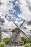 Molino de viento holandés contra un fondo azul nublado imagen de archivo