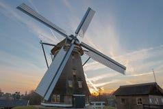 Molino de viento holandés en la puesta del sol Fotos de archivo