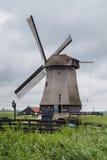 Molino de viento holandés en una configuración del paisaje del pantano imágenes de archivo libres de regalías