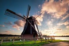 Molino de viento holandés encantador por el lago en la puesta del sol Imagenes de archivo
