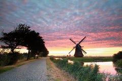 Molino de viento holandés por el camino en la salida del sol dramática Imágenes de archivo libres de regalías
