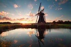 Molino de viento holandés por el lago en el sol abajo Imagenes de archivo