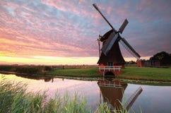 Molino de viento holandés por el río en la salida del sol Fotos de archivo libres de regalías