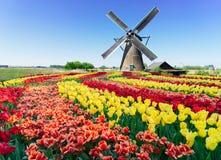 Molino de viento holandés sobre las aguas de río fotos de archivo