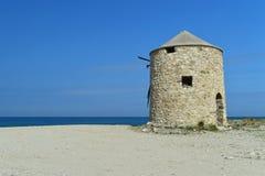 Molino de viento piedra-construido abandonado viejo en la playa arenosa de Lefkada Fotos de archivo