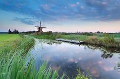Molino de viento por el río en la puesta del sol Imágenes de archivo libres de regalías
