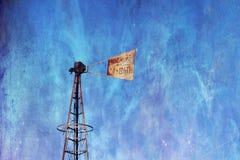 Molino de viento quebrado contra azul Foto de archivo