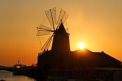 Molino de viento salino de Sicilia del verano del marsala de la puesta del sol imágenes de archivo libres de regalías