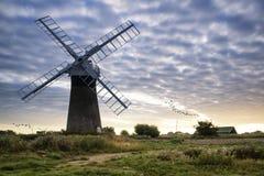 Molino de viento viejo de la bomba en madrugada inglesa del paisaje del campo Foto de archivo libre de regalías