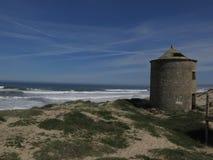 Molino de viento viejo en el océano imagen de archivo