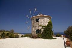 Molino de viento viejo en la isla de Grecia en la playa del mar Imagenes de archivo