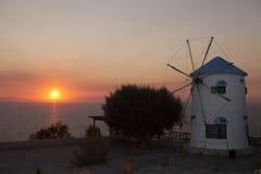Molino de viento viejo en la isla de Grecia en la playa del mar Imagen de archivo libre de regalías