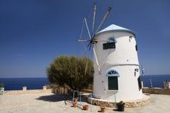 Molino de viento viejo hermoso en la isla de Grecia en la playa del mar Imagen de archivo