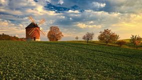 Molino de viento viejo hermoso Foto del paisaje con arquitectura en la hora de oro de la puesta del sol Chvalkovice - República C foto de archivo