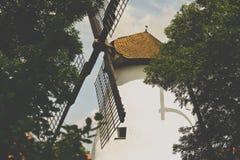 Molino de viento viejo visto a través de árboles verdes Fotos de archivo