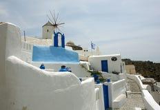 Molino de viento y edificio azul en la isla de Santorini Imagen de archivo libre de regalías