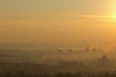 Molino del fertilizante que contamina la atmósfera con humo y niebla con humo imagen de archivo