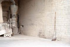 Molino eléctrico del maíz y escoba de madera en la pared Fotos de archivo libres de regalías