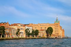 Molino Stucky building and houses along La Giudecca Canal in Venice, Italy. Venice is situated across a group of 117 small islands that are separated by canals royalty free stock image
