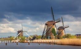 Molinoes de viento contra el cielo nublado en la puesta del sol en Kinderdijk, Netherland Imagenes de archivo
