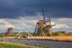 Molinoes de viento contra el cielo nublado en la puesta del sol en Kinderdijk, Netherland Fotos de archivo libres de regalías