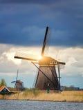 Molinoes de viento contra el cielo nublado en la puesta del sol en Kinderdijk, Netherland Foto de archivo libre de regalías